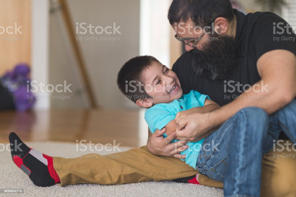 Native American dad wrestles and plays with his son in living room stock photo