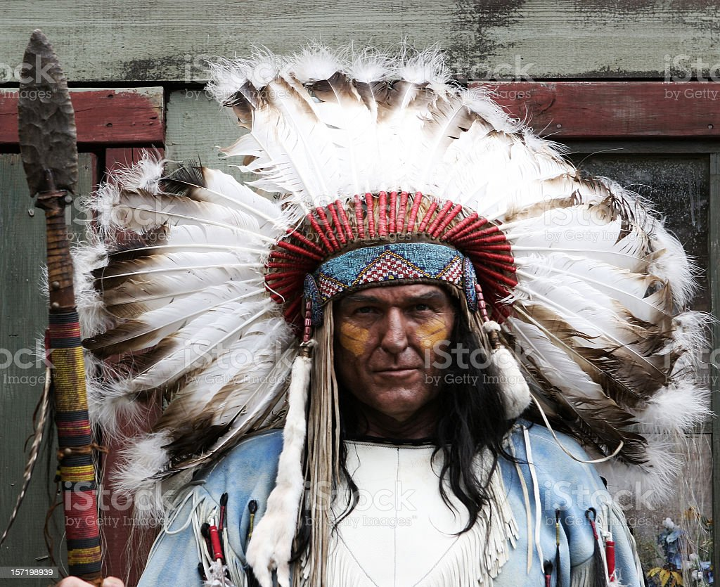 Native American man with feather headdress and spear royalty-free stock photo
