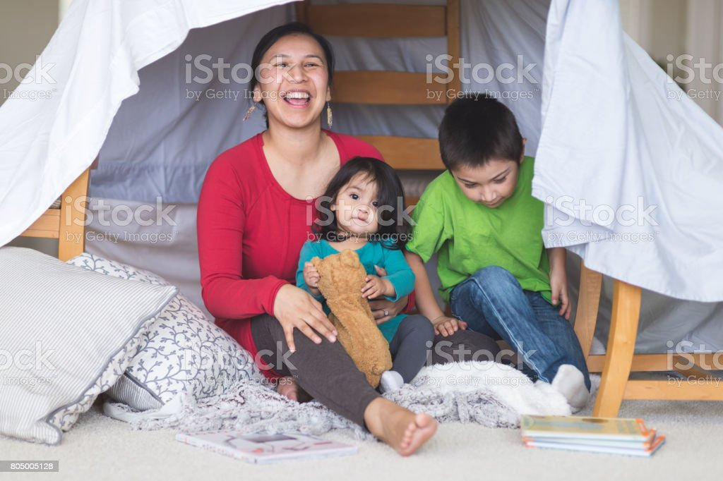 Native American mom plays with her daughter and son under makeshift fort in living room stock photo