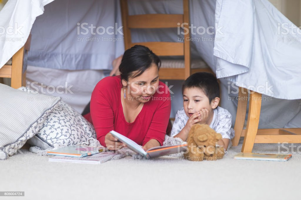Native American mom reads with her son under makeshift fort in living room stock photo