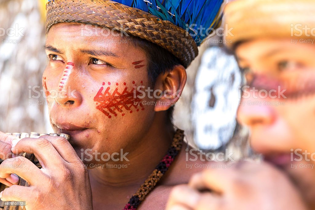 Native Brazilian guys playing wooden flute stock photo