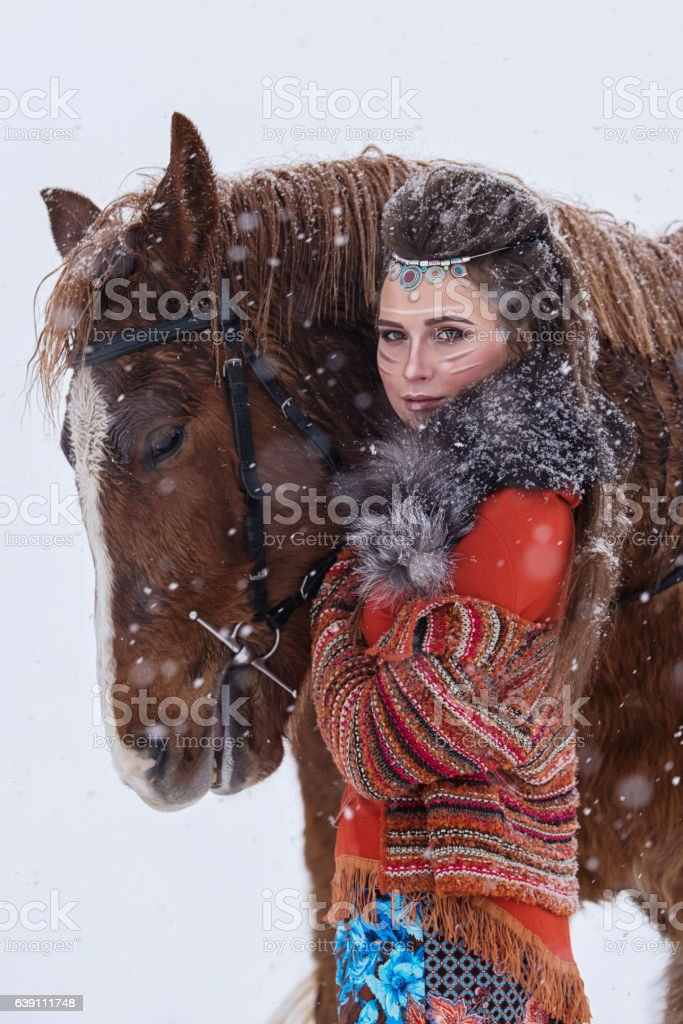 Native indian woman with traditional makeup and hairstyle in winter. stock photo