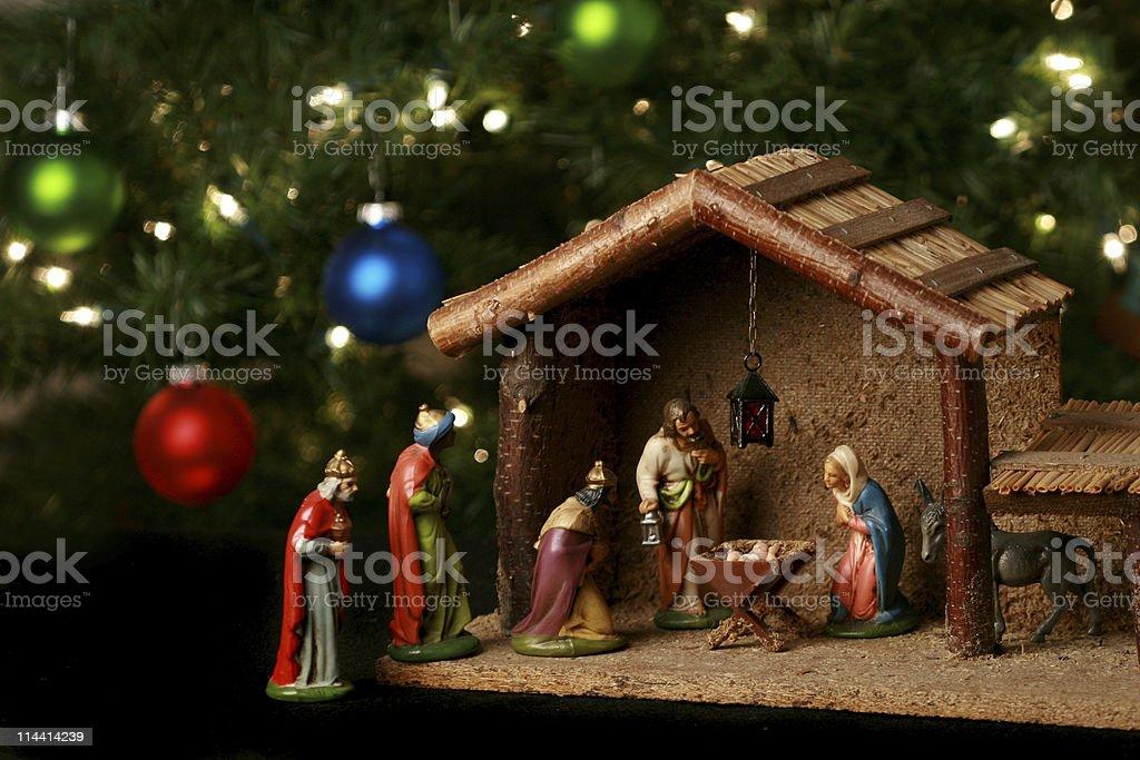 Nativity scene next to a Christmas tree stock photo