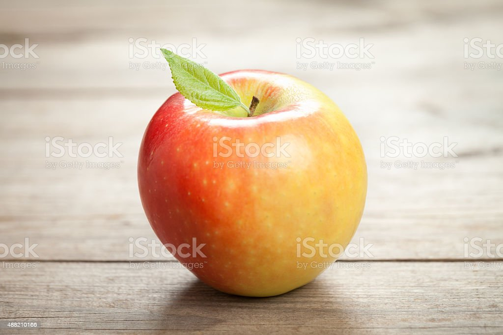 Natural apple with leaf on old wooden table stock photo