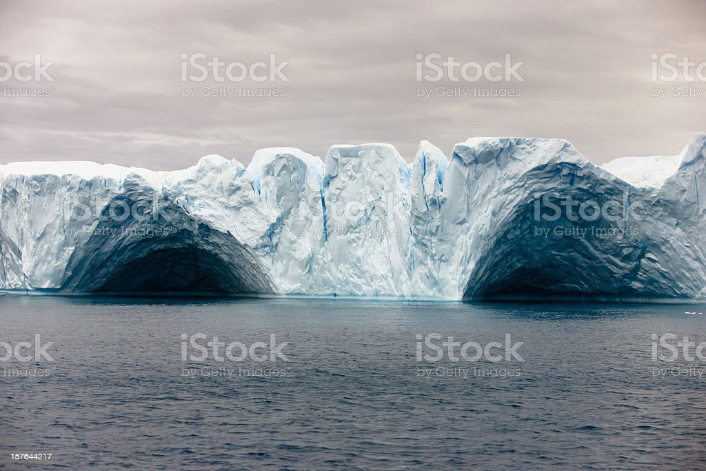 Natural Arch in Tabular Iceberg Greenland Arctic Ocean stock photo