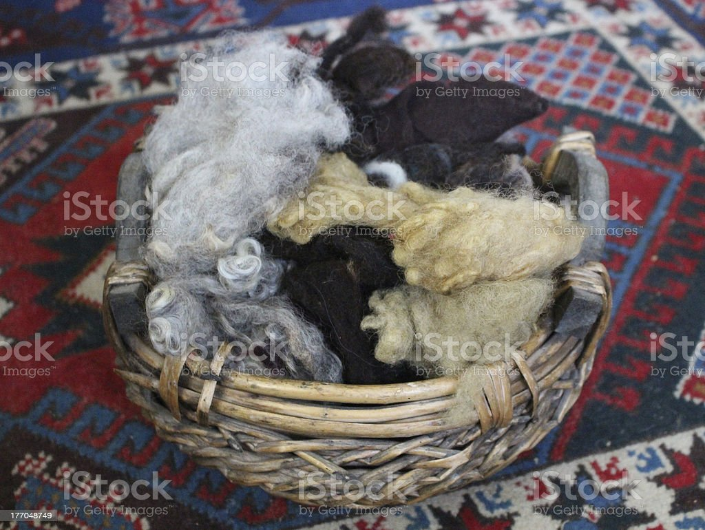 Natural basket filled with raw wool fleece royalty-free stock photo