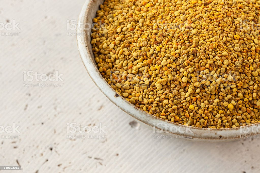 Natural bee pollen in ceramic bowl on concrete stock photo