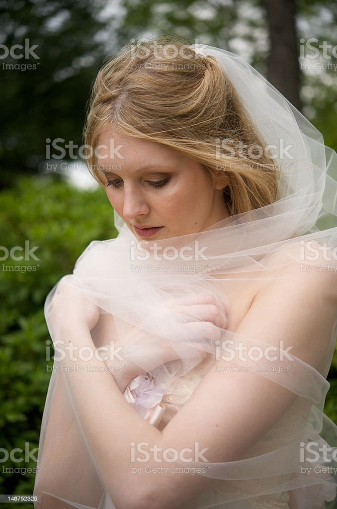 Natural bride wrapped up in veil stock photo