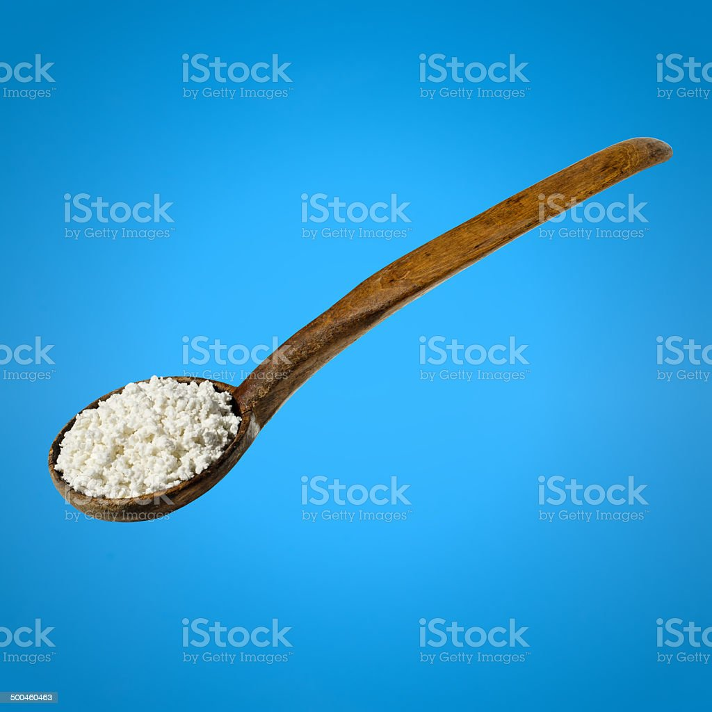 Natural cheese in a wooden spoon stock photo