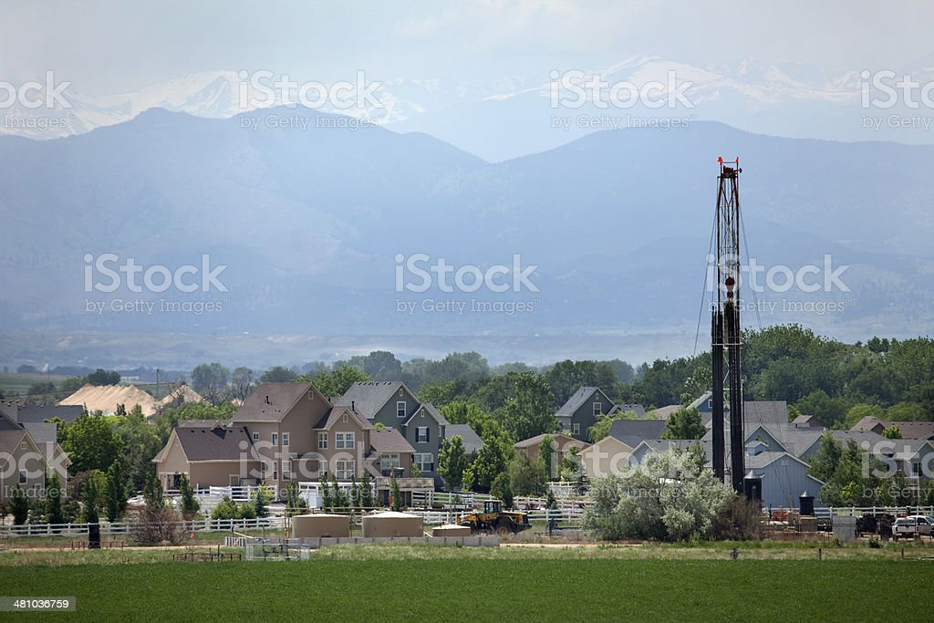 Natural gas drill rig with homes and Colorado Rocky mountains stock photo