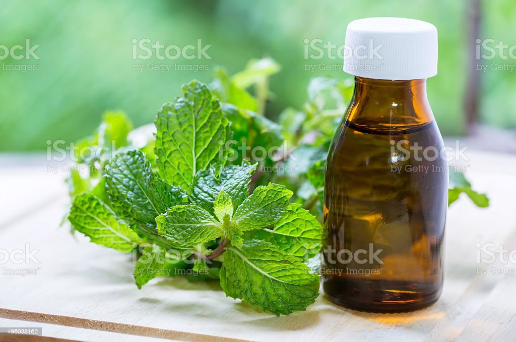 Natural Mint Essential Oil in a Glass Bottle stock photo