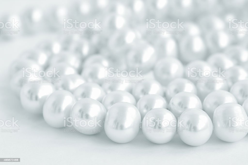 Natural pearl necklace on white background, blue tinted stock photo