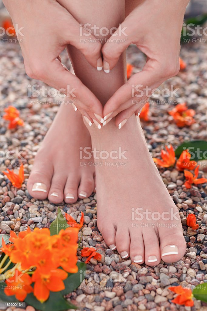 Natural Pedicure and Manicure with Orange Star Flowers in Nature royalty-free stock photo