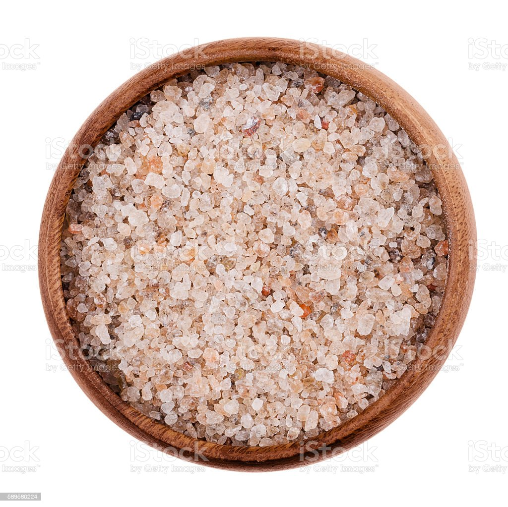 Natural red rock salt in a bowl on white background stock photo
