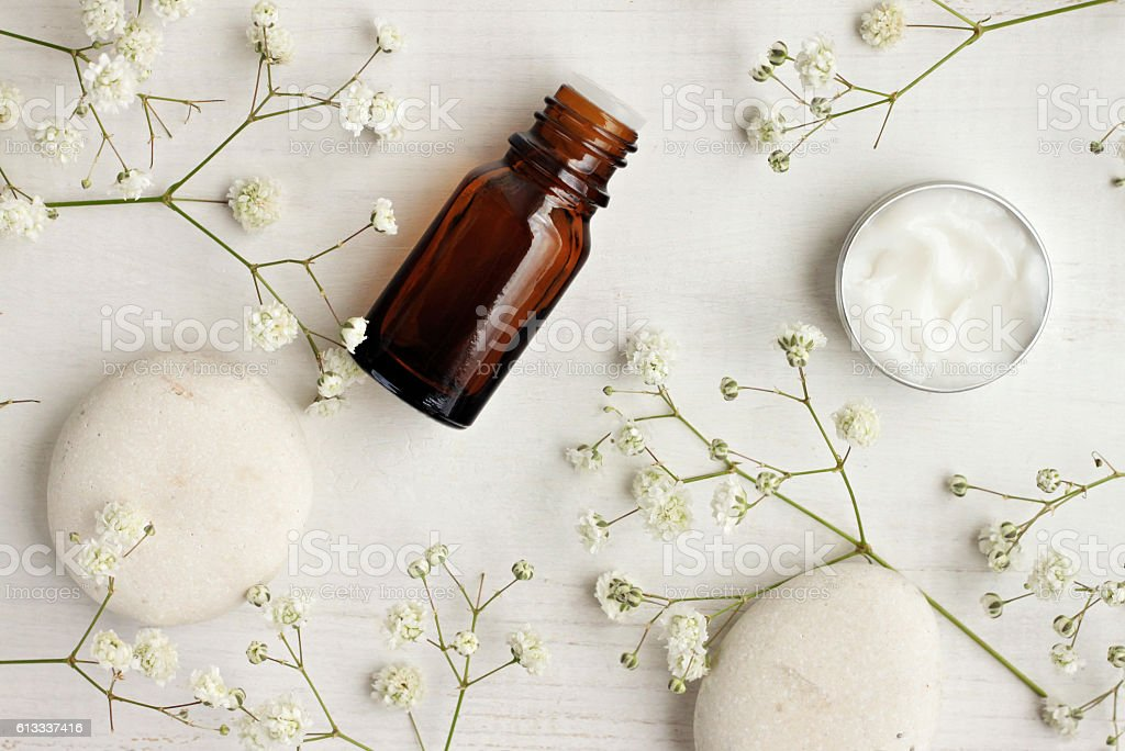 Natural skincare products,white stones and flowers, top view. stock photo