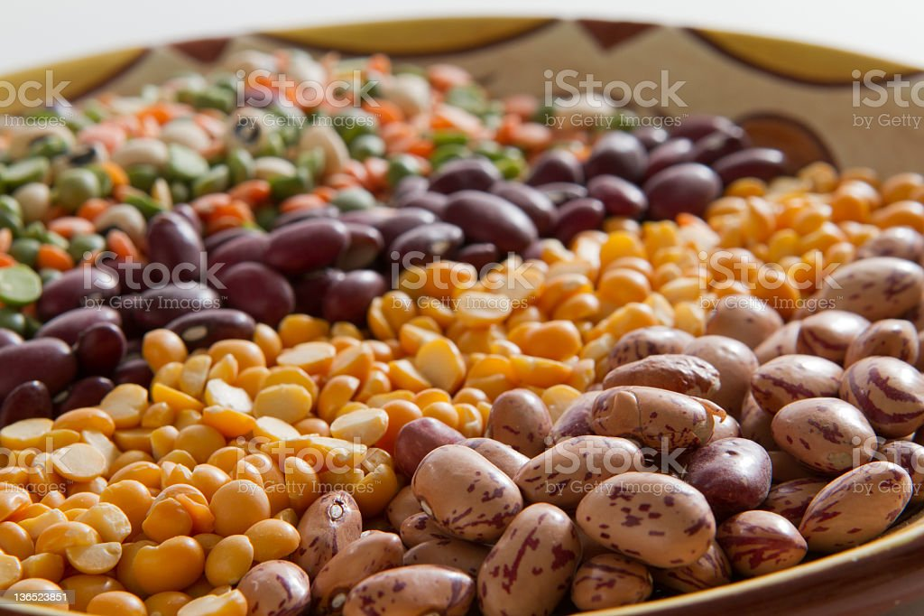 Natural toned bowl holds 9 different raw beans or peas. stock photo