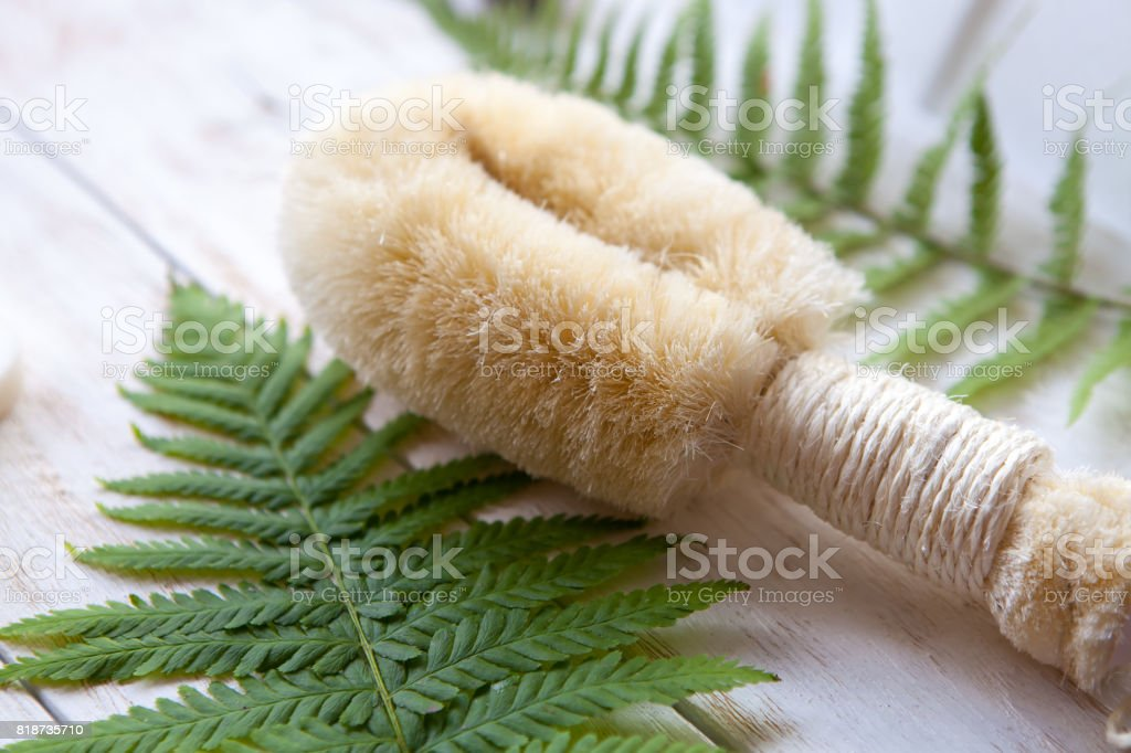 Natural Washcloth with Fern on white wooden background Spa resort and wellness composition. stock photo