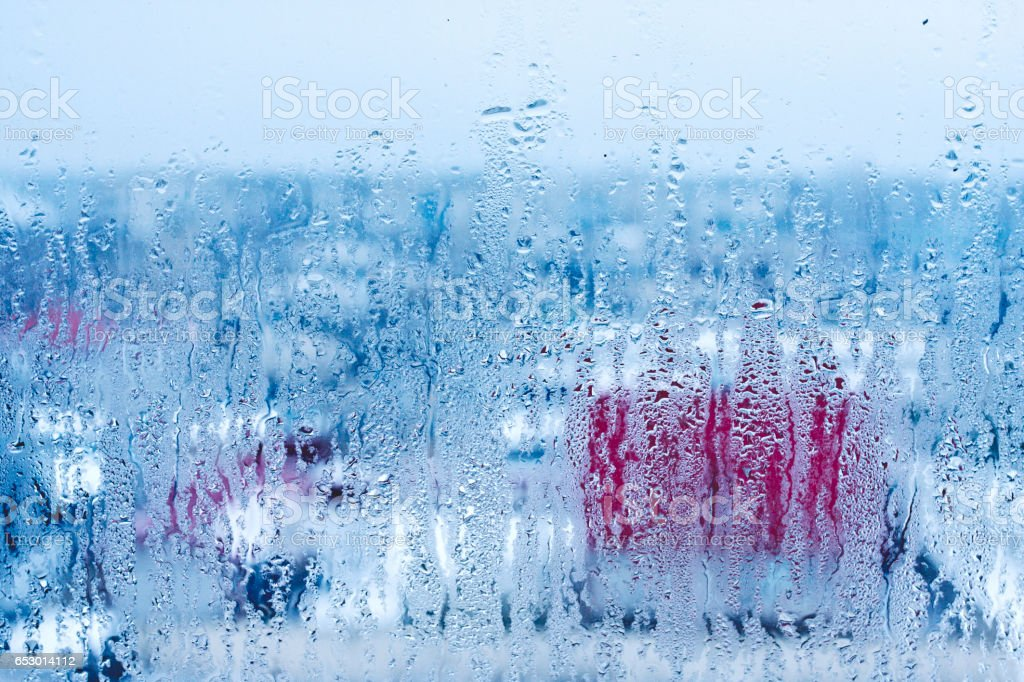 Natural water drops on glass, window glass with condensation, strong, high humidity, large drops of water flow down the window, cold tone stock photo
