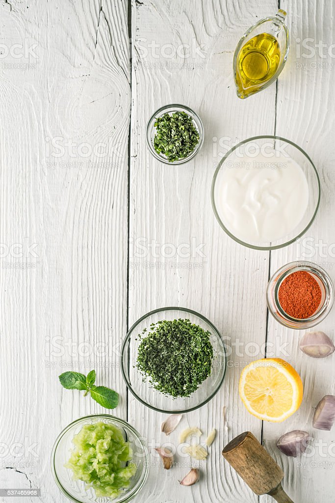 Natural yogurt and different seasoning on white wooden table vertical stock photo