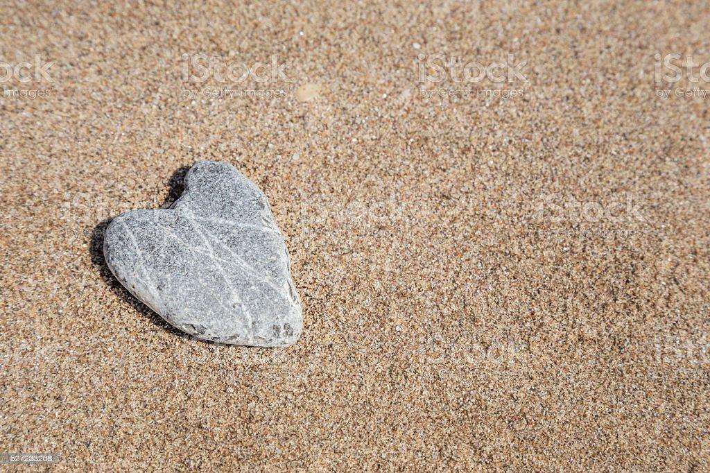 naturally heart shaped stone on sand stock photo