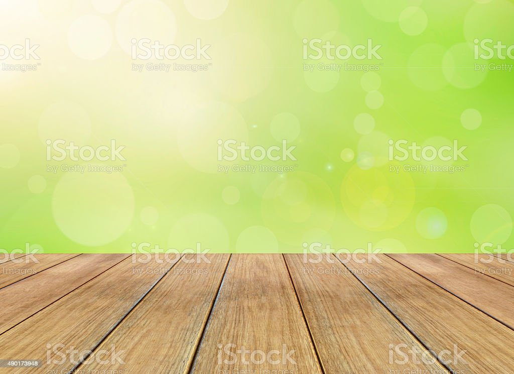 Nature bright spring background with sunlight bokeh and wooden floor stock photo