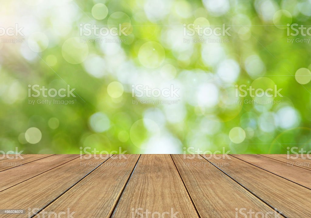Nature bright spring background with sunlight bokeh and wooden plank stock photo