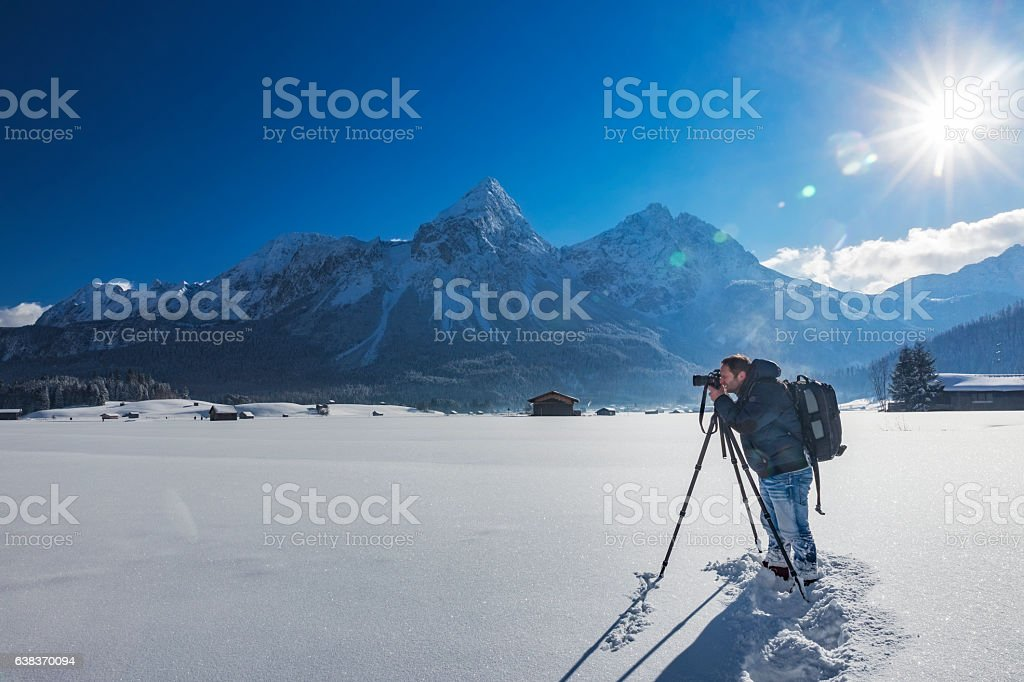Nature photographer at winter in front of Mount Grünstein stock photo