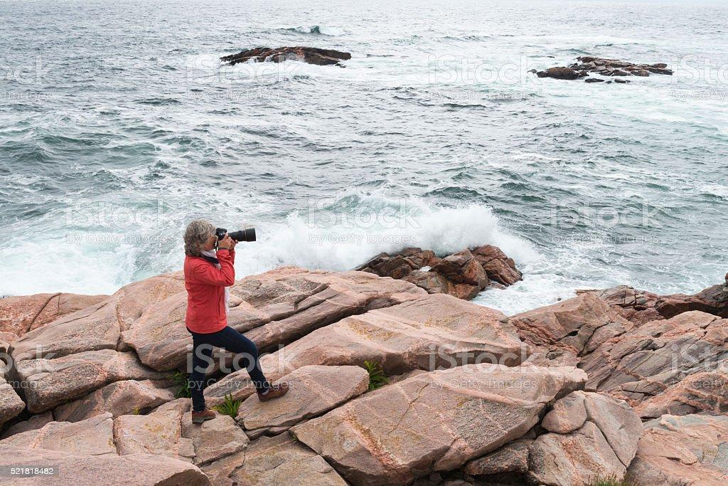 Nature photographer on coastline, woman photographing stock photo