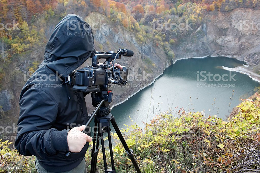 A nature photographer with camera, looking out over a lake stock photo