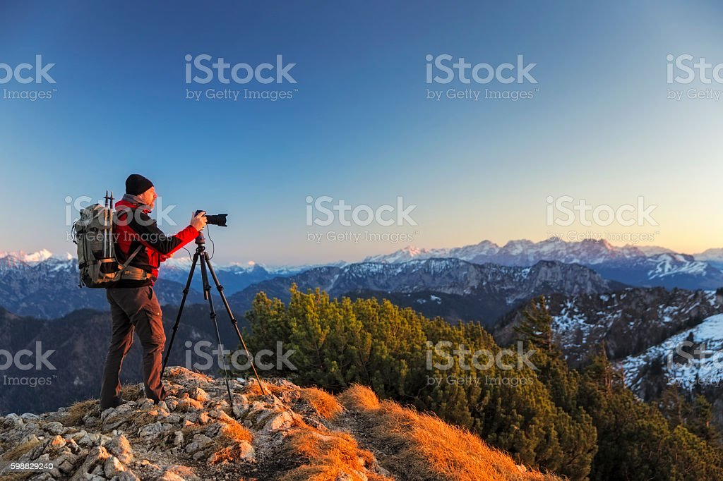 Nature photographer with tripod an backpack  in the alps stock photo