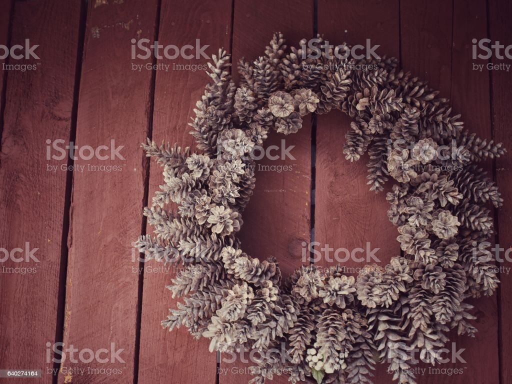 Nature Pinecone Wreath Outdoor Holiday Decoration, Red Barn Wood Planks stock photo