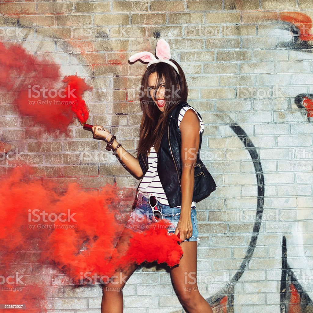 Naughty girl in pink rabbit ears with red smoke bombs stock photo