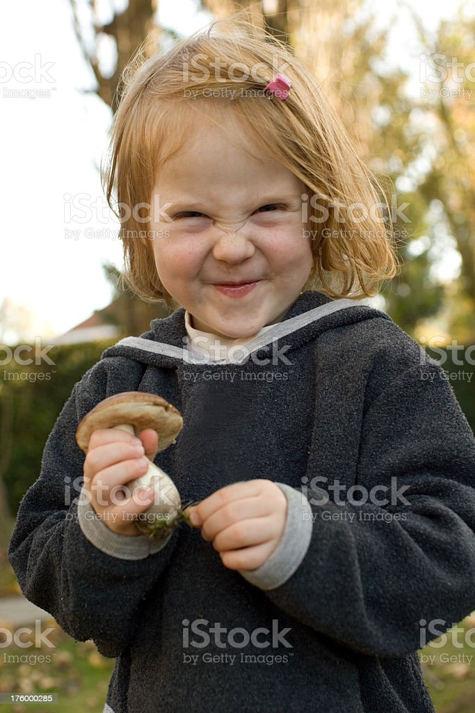 Naughty little blonde girl picked a mushroom royalty-free stock photo