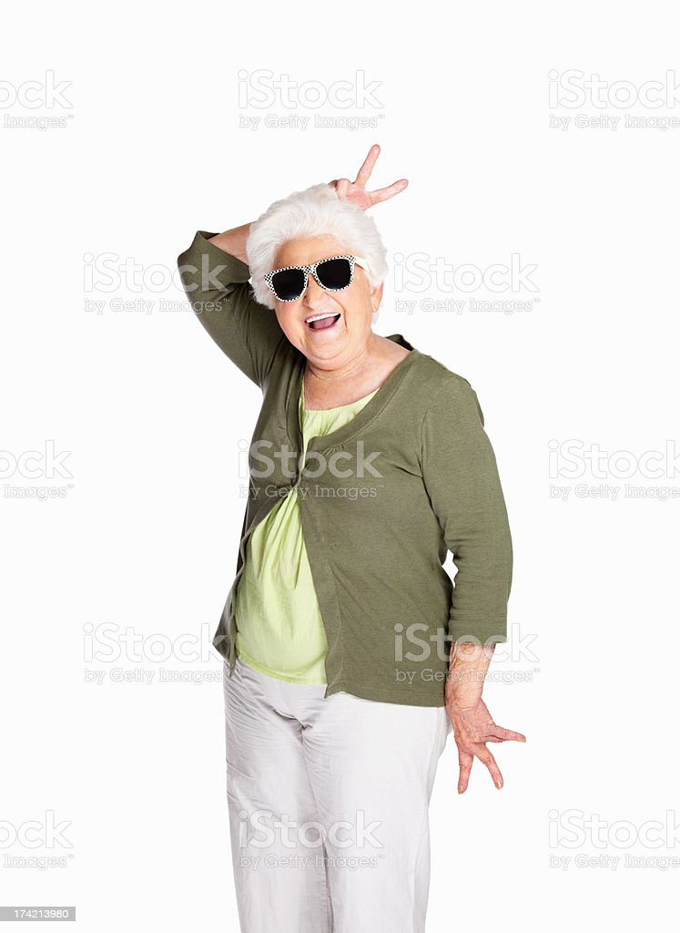 Naughty senior female wearing sunglasses isolated against white stock photo