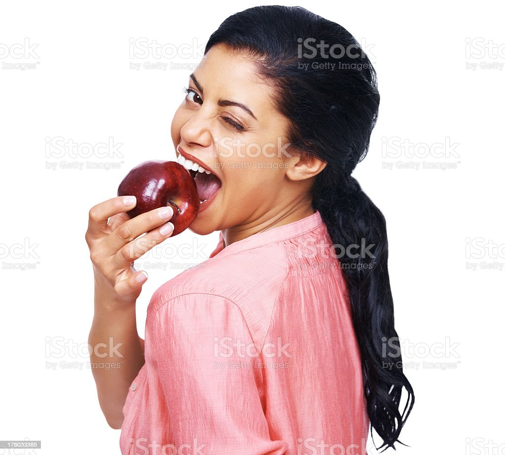 Naughty young woman eating an apple and winking on white stock photo