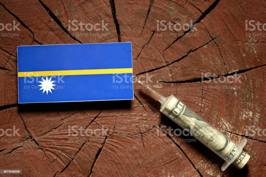 Nauru flag on a stump with syringe injecting money in flag stock photo