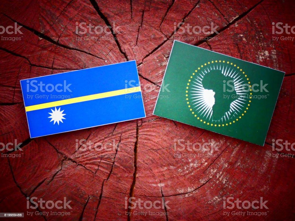 Nauru flag with African Union flag on a tree stump isolated stock photo
