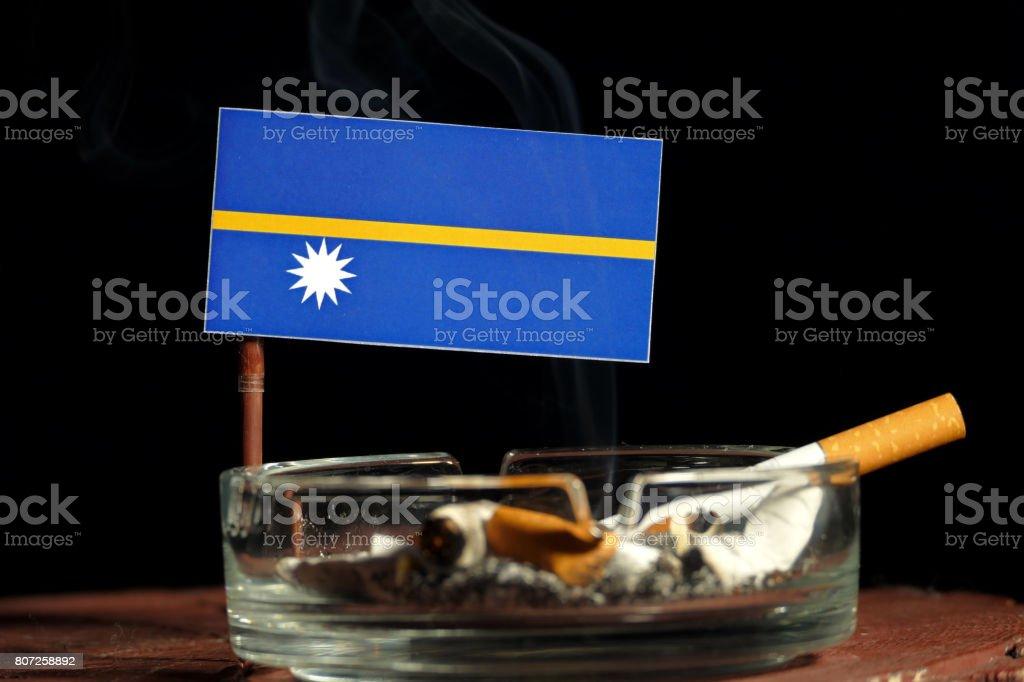 Nauru flag with burning cigarette in ashtray isolated on black background stock photo