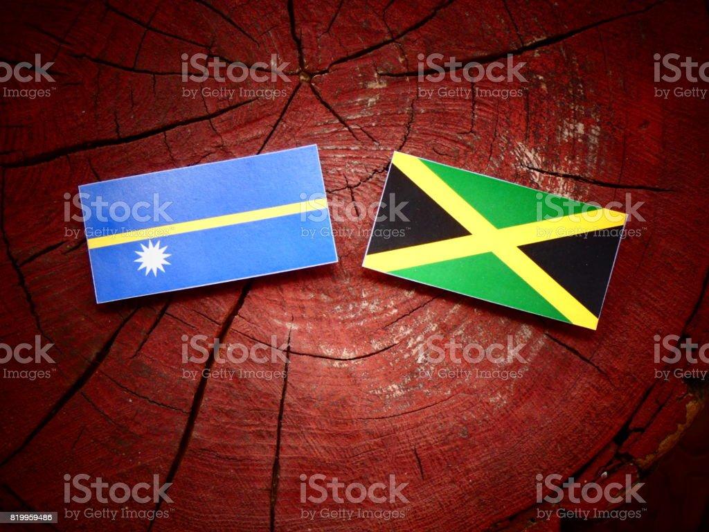Nauru flag with Jamaican flag on a tree stump isolated stock photo