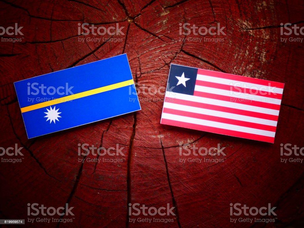 Nauru flag with Liberian flag on a tree stump isolated stock photo