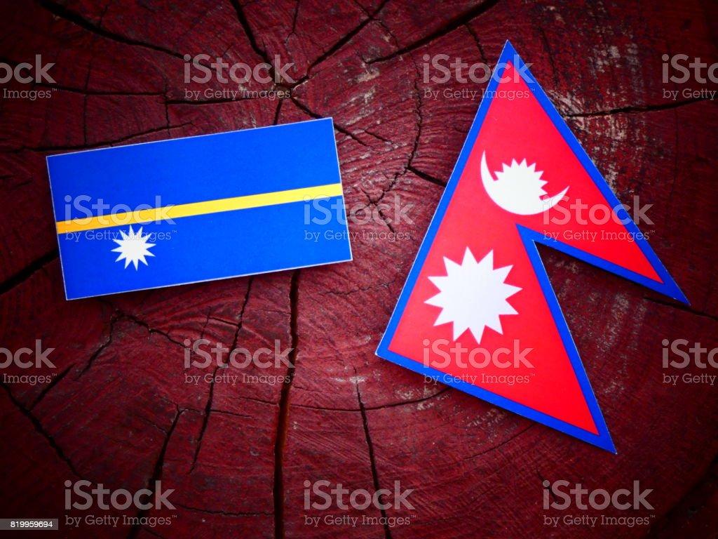 Nauru flag with Nepali flag on a tree stump isolated stock photo