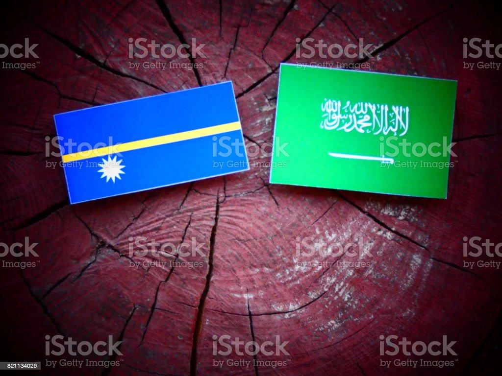 Nauru flag with Saudi Arabian flag on a tree stump isolated stock photo