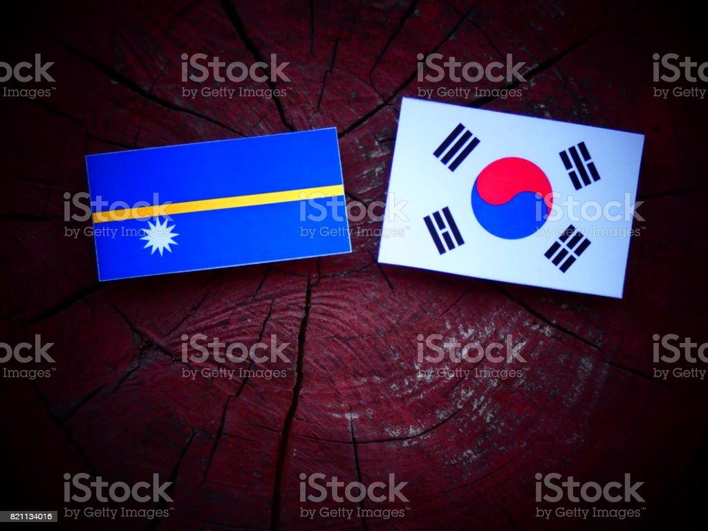 Nauru flag with South Korean flag on a tree stump isolated stock photo