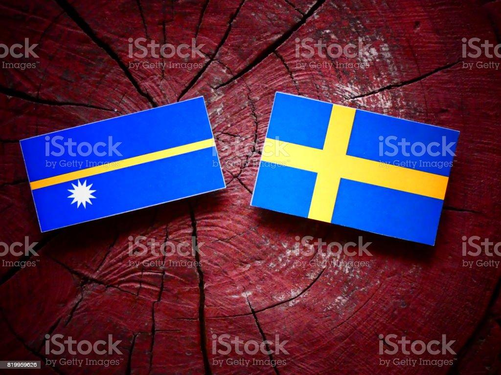 Nauru flag with Swedish flag on a tree stump isolated stock photo