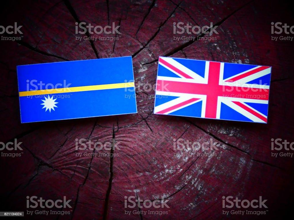 Nauru flag with UK flag on a tree stump isolated stock photo