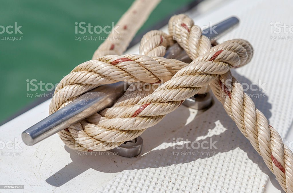 Nautical knot rope tied around stake on boat or ship stock photo