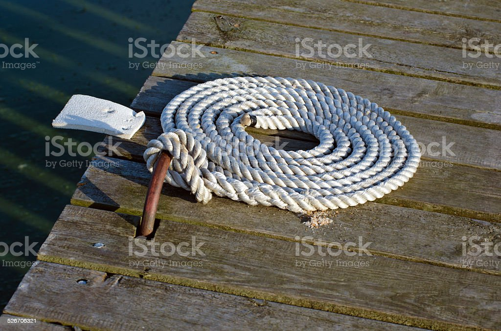 nautical mooring rope on wooden pier stock photo