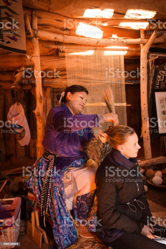 Navajo woman brushes hair with straw stock photo