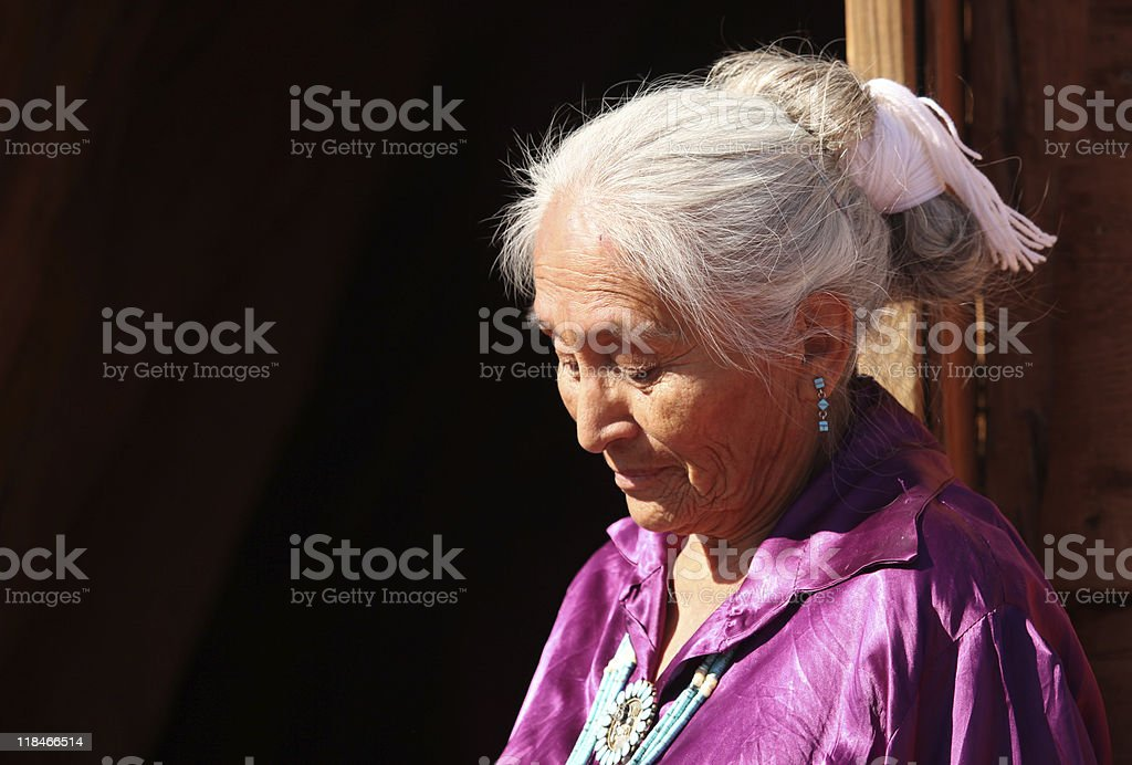 Navajo Woman Looking Down Outdoors in Bright Sun stock photo