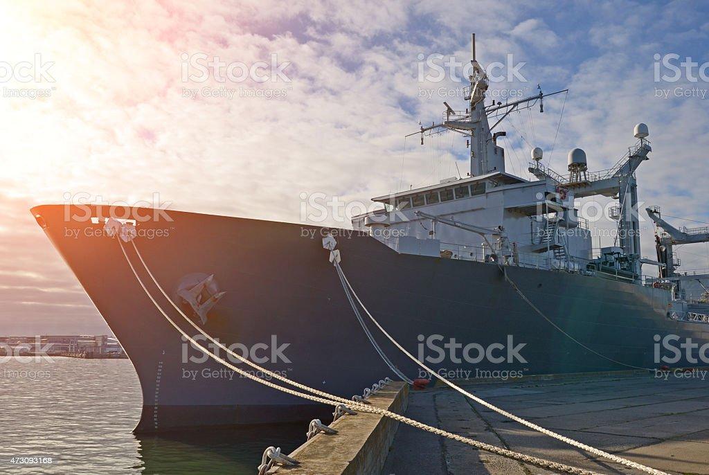 Naval auxiliary ship docked at the harbor. stock photo